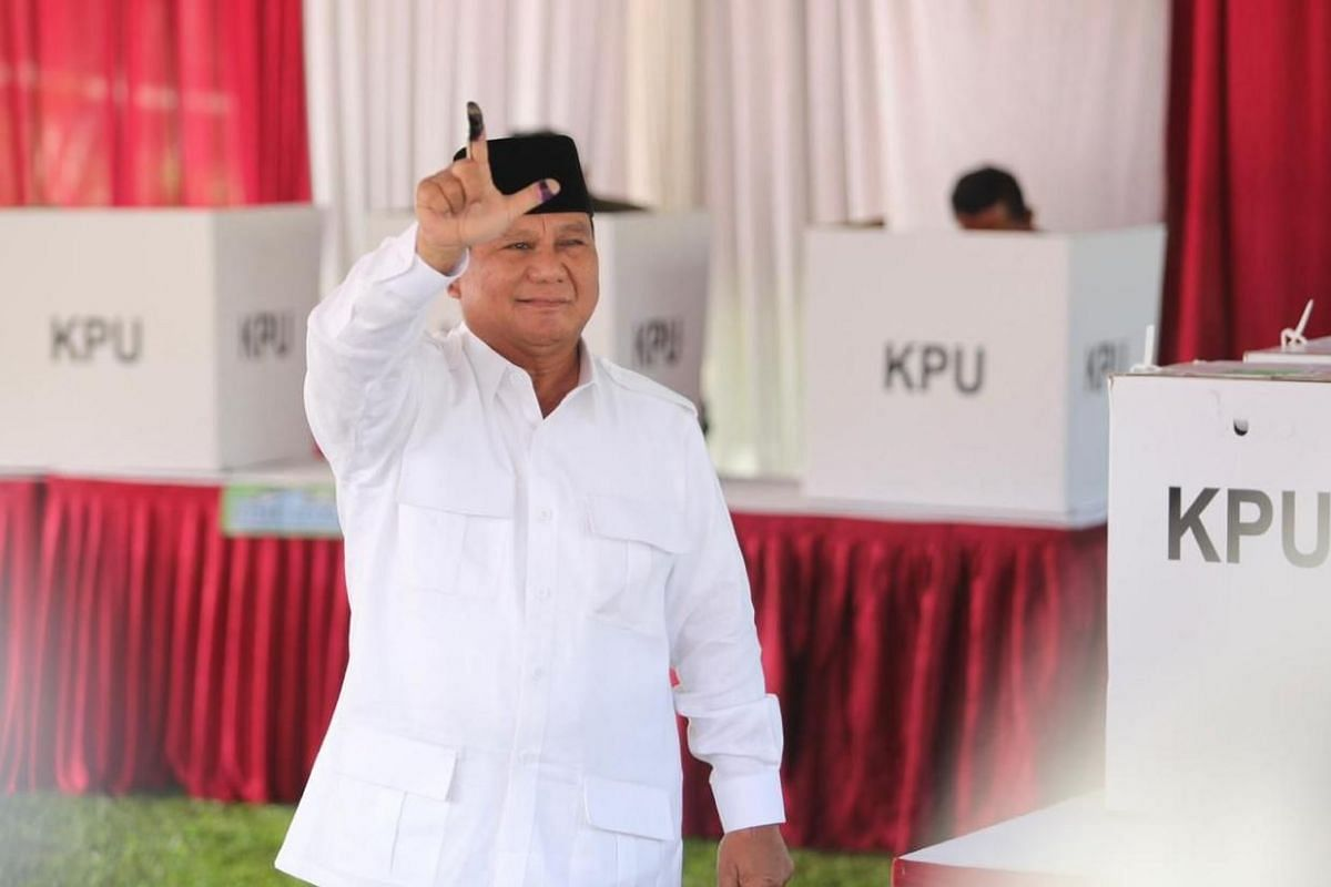 Indonesia's presidential hopeful Prabowo Subianto smiles for the cameras after voting in Bojeng Koneng, West Java, on April 17, 2019.