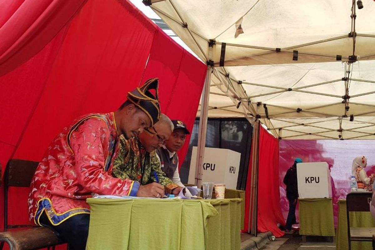 Election committee officials in Chinese costumes at a polling station in Cibadak. The area is home to one of the largest Chinese communities in Bandung.