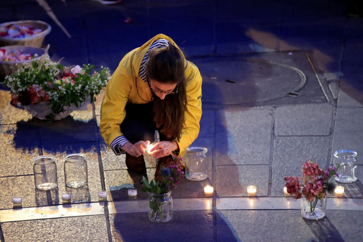 A woman lights a candle at the Place Saint-Michel the day after Notre-Dame Cathedral suffered heavy damage from a massive fire that devastated large parts of the Gothic structure in Paris, France, on April 16, 2019.