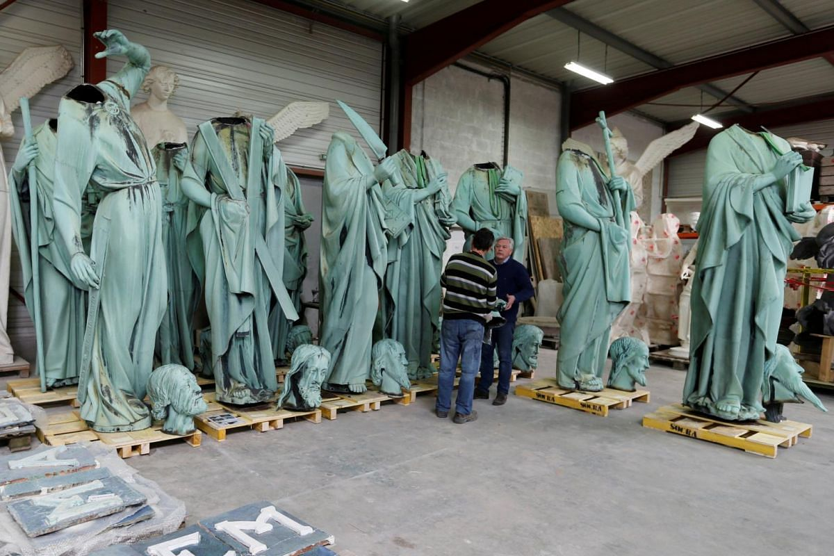 Consultant Patrick Palem (right) checks statues that were removed from the spire of Paris' Notre-Dame Cathedral, in a workshop at the Socra company for restoration work in Marsac-sur-L'Isle, on April 16, 2019.