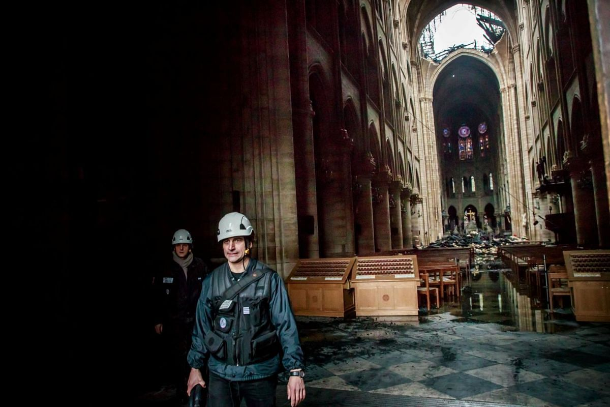 A staff member walks inside Notre-Dame Cathedral in the aftermath of the fire, on April 16, 2019.