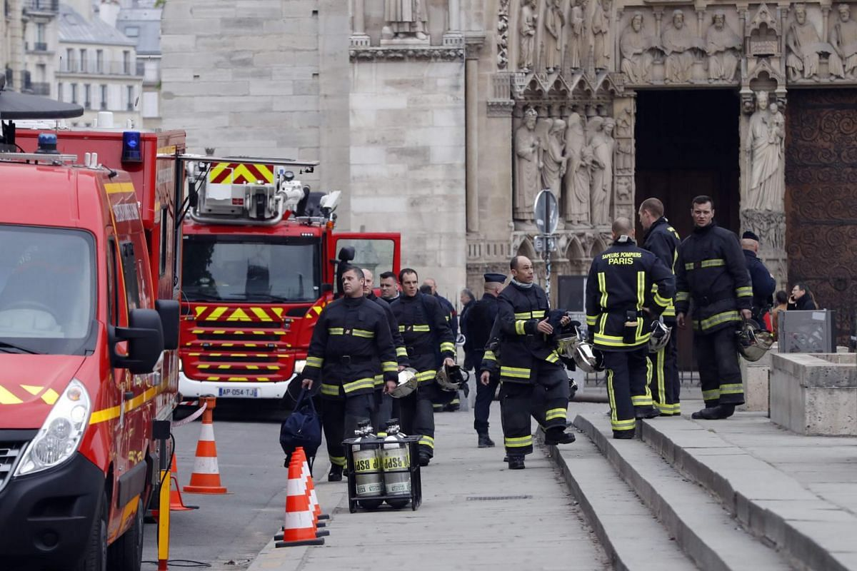 Firefighters are seen outside Notre-Dame Cathedral a day after the fire, on April 16, 2019.