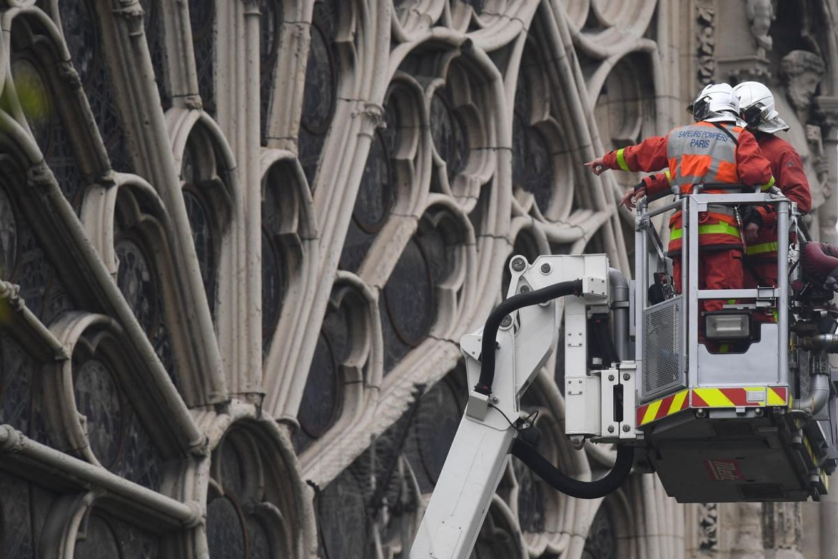 Firefighters assess the damage to Notre-Dame Cathedral in Paris on April 16, following a fire which destroyed much of the building a day earlier.