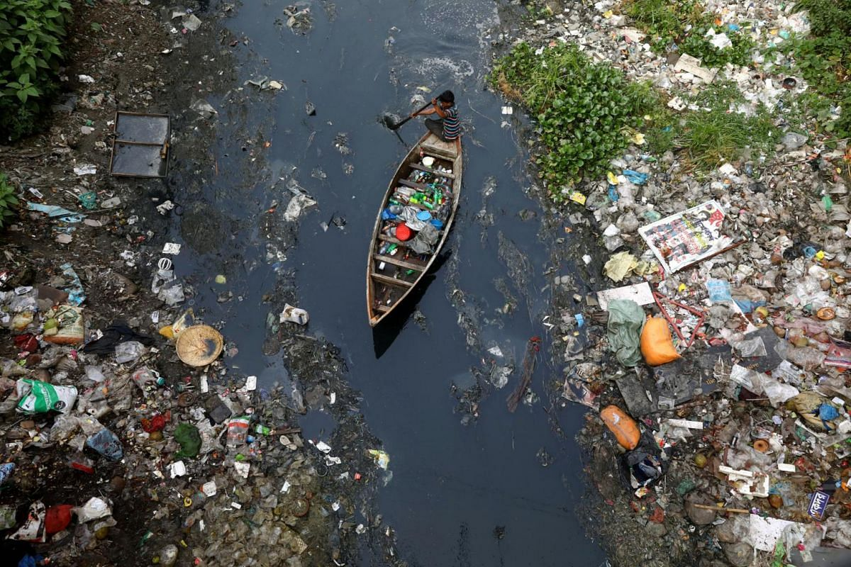 A man on a boat collects plastic materials from dirty water in Dhaka, Bangladesh, on April 17, 2019.