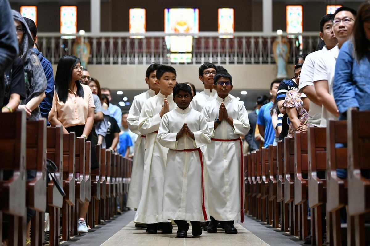 Altar Servers walking in silence towards the Altar at the beginning of the 5pm Service at St Joseph's Church, on April 19, 2019.