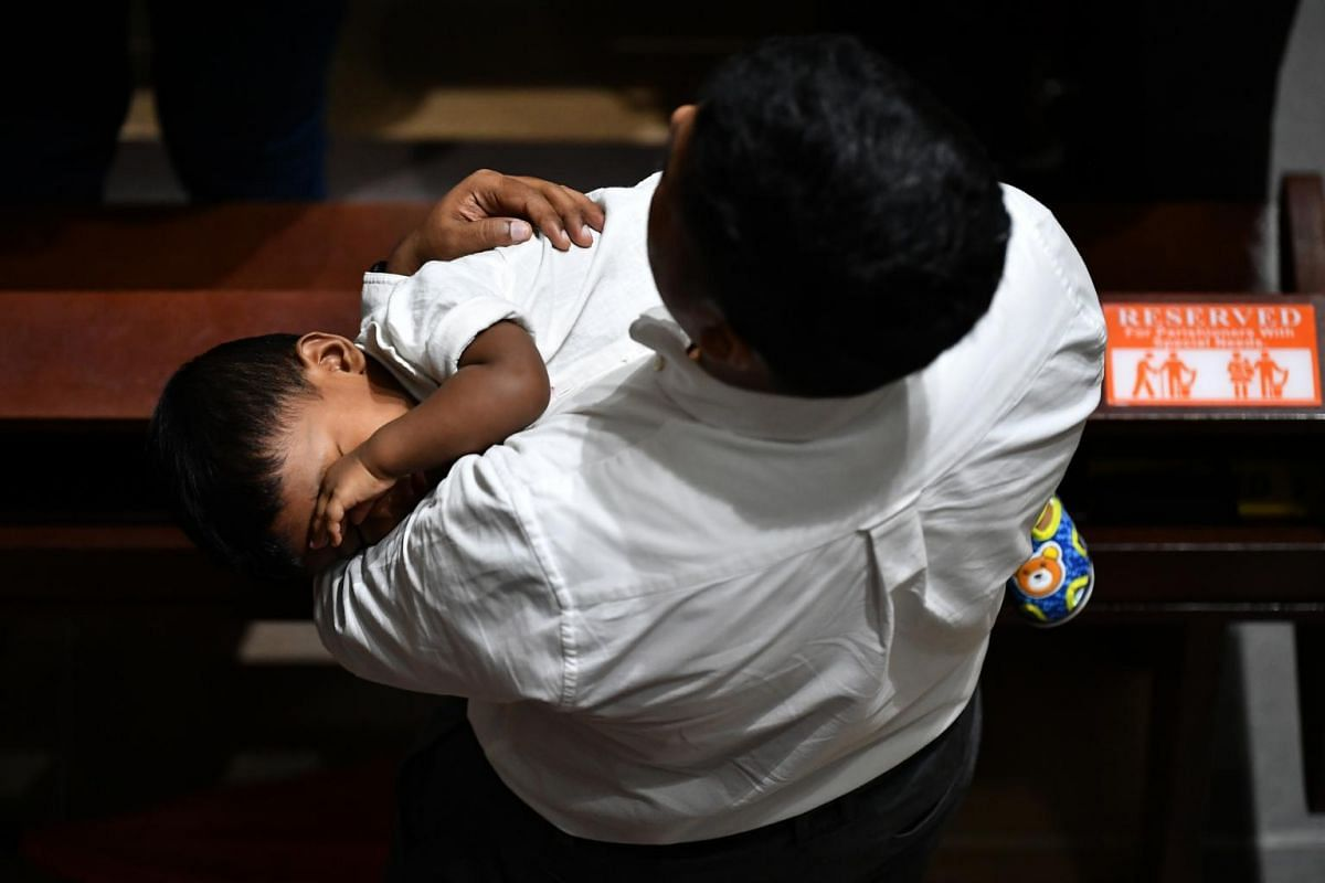 A parishioner holding a child at the 5pm service at St Joseph's Church, on April 19, 2019.