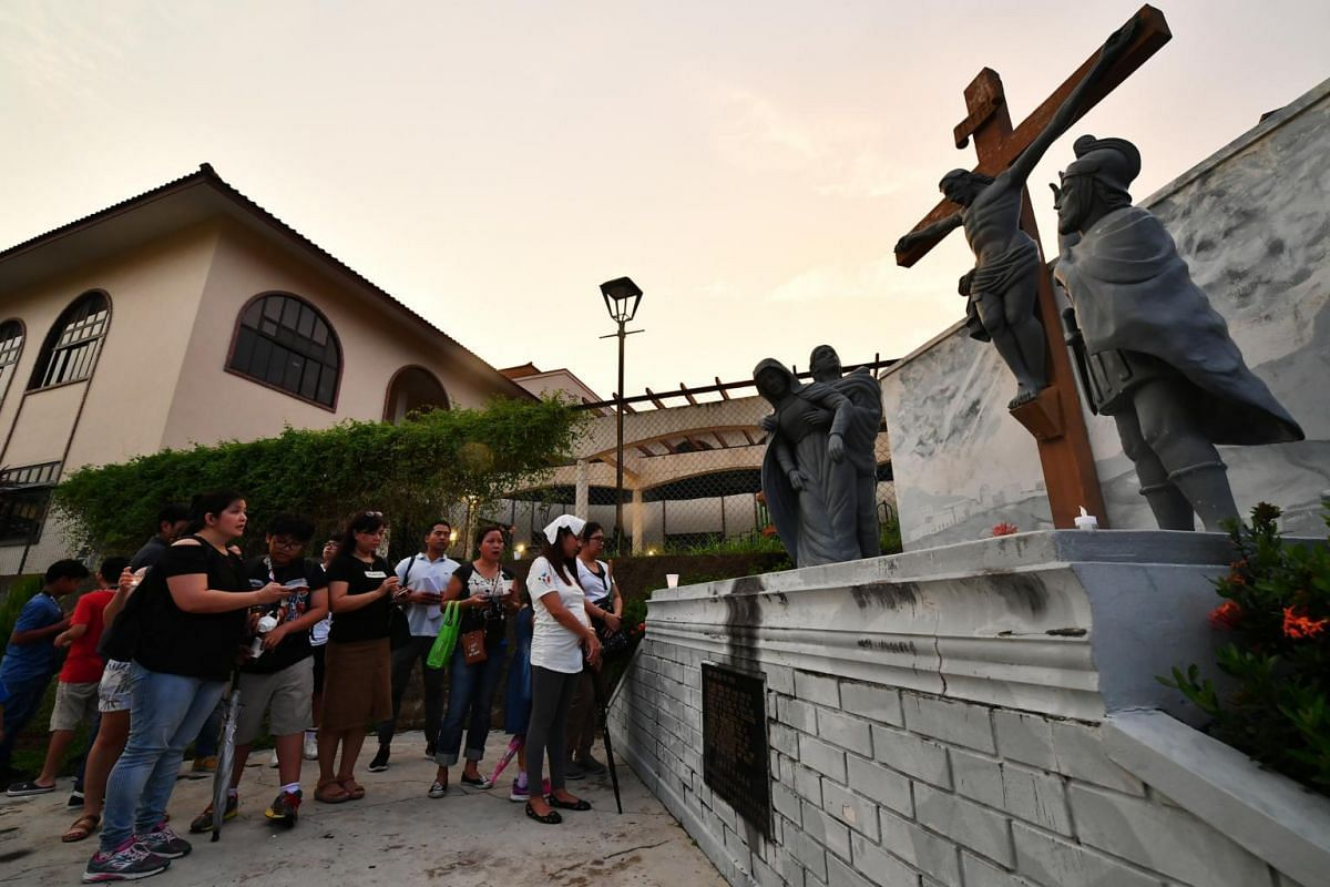 Worshippers praying at the 12th Station - Jesus dies on the cross, which is one of the Stations of the Cross at St Joseph's Church, on April 19, 2019.