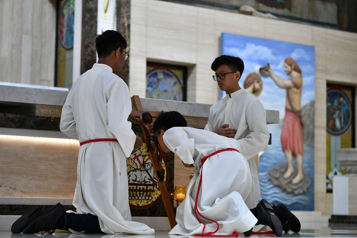 One of the Altar Servers kissing the Crucifix during the 5pm service to pay reverence to Jesus who died on the Cross, at St Joseph's Church, on April 19, 2019.