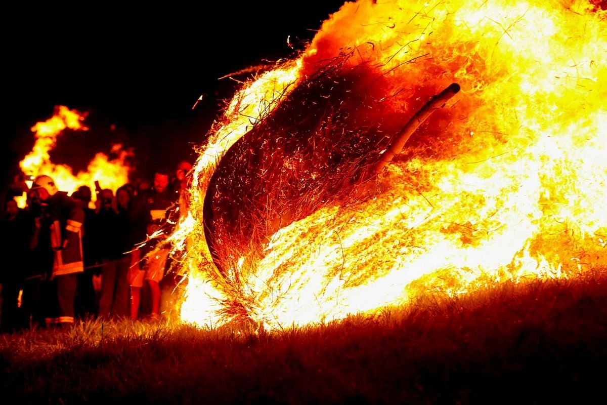 A wooden wheel wich has been stuffed with straw and set alight rolls down a hill during the celebration of the traditional 'Osterraederlauf' in Luegde, Germany, April 21, 2019. PHOTO: REUTERS