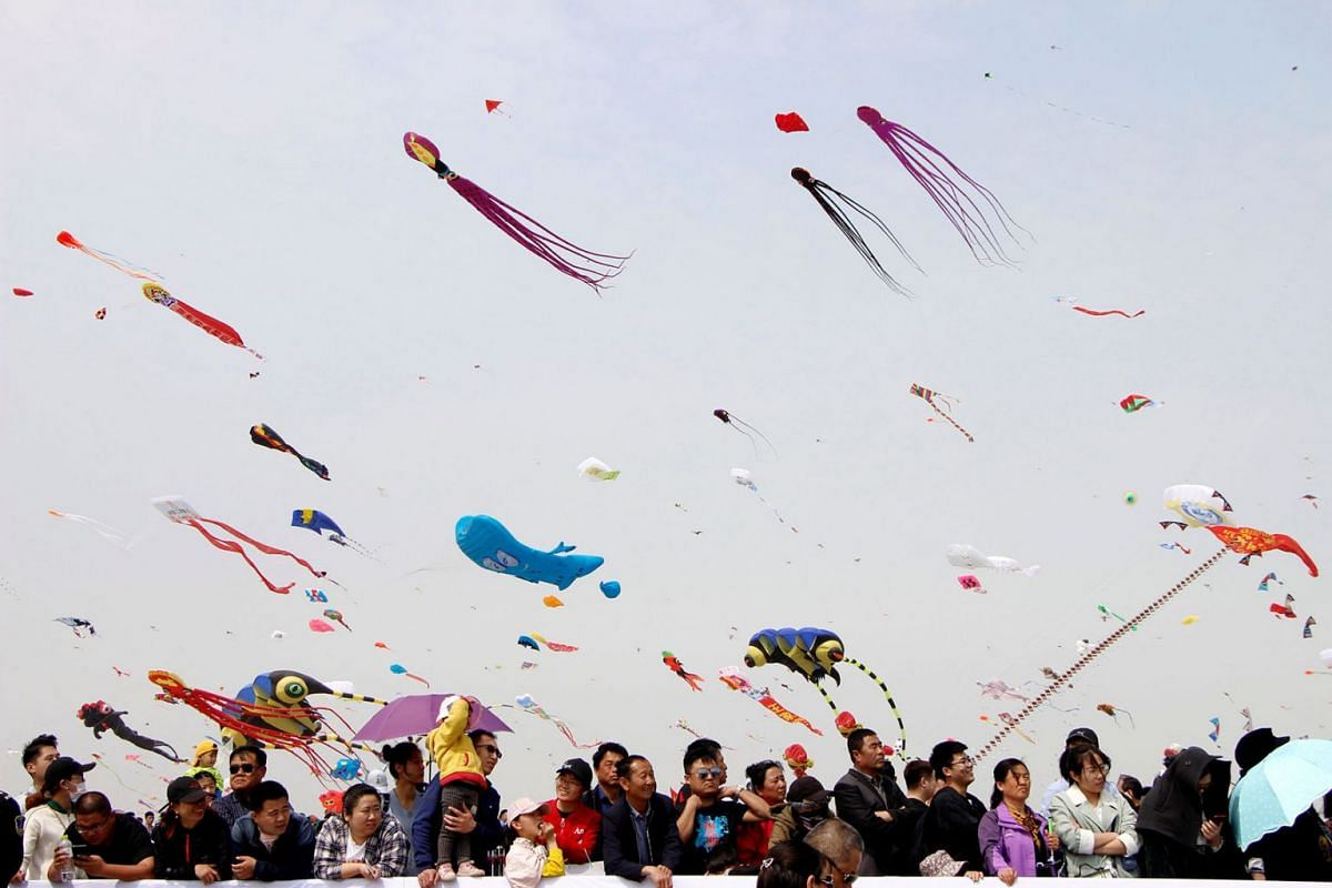 People look on as kites in various shapes fly in the sky during the International Kite Festival in Weifang, Shandong province, China April 20, 2019. PHOTO: REUTERS