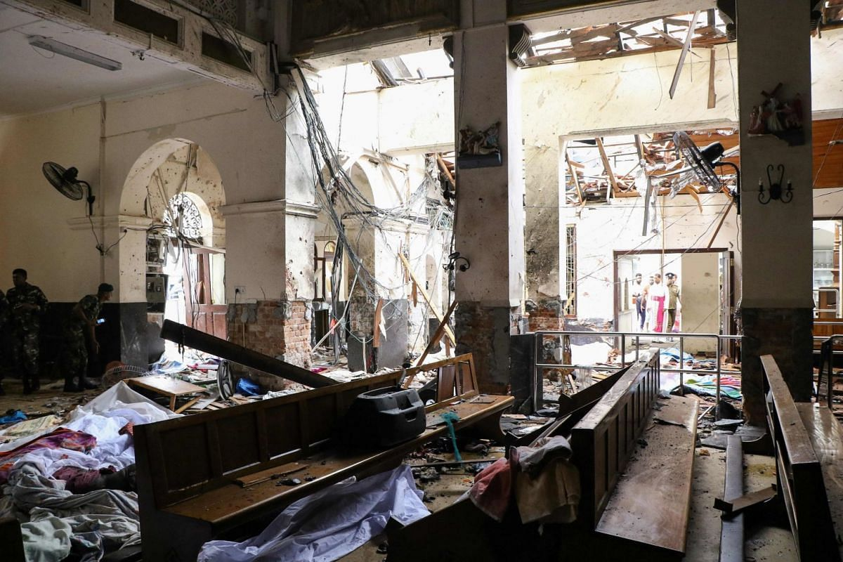 Dead bodies are covered with blankets amid blast debris at St Anthony's Shrine following an explosion at the church in Kochchikade in Colombo, on April 21, 2019.