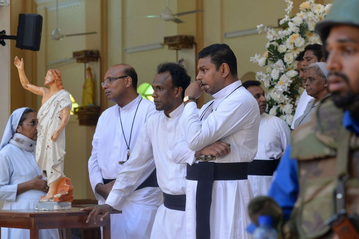 Catholic priests stand inside the church after a bomb blast in Negombo, Sri Lanka, on April 21, 2019.