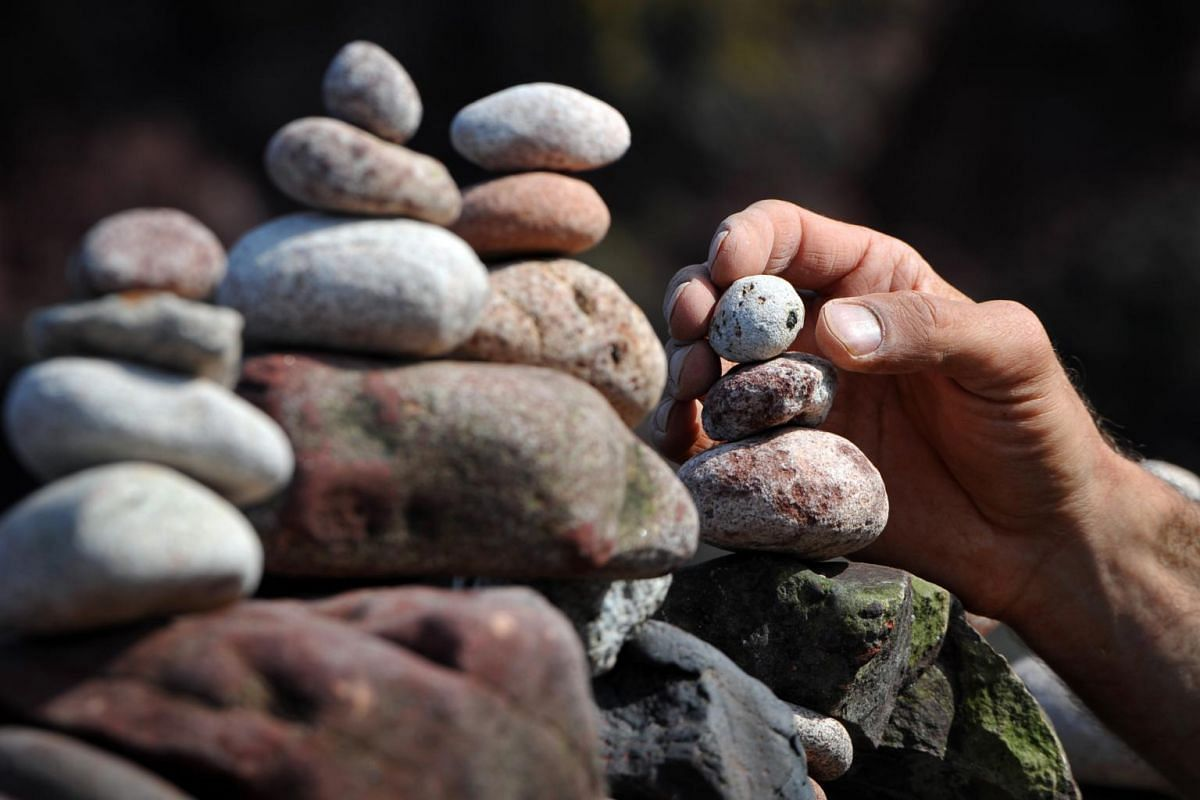 A participant carefully places a stone during the European Stone Stacking Championships 2019.