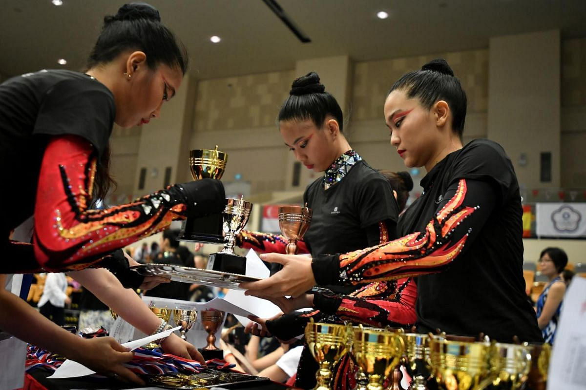 (From left) Ms Phebe Lau, 18, Ms Michele Lau, 18 and Ms Jolene Tan, 27, preparing medals and trophies during the award ceremony for the Aesthetic Group Gymnastics Four Continents Championships/Singapore Cup event at Our Tampines Hub, on April 3, 2019