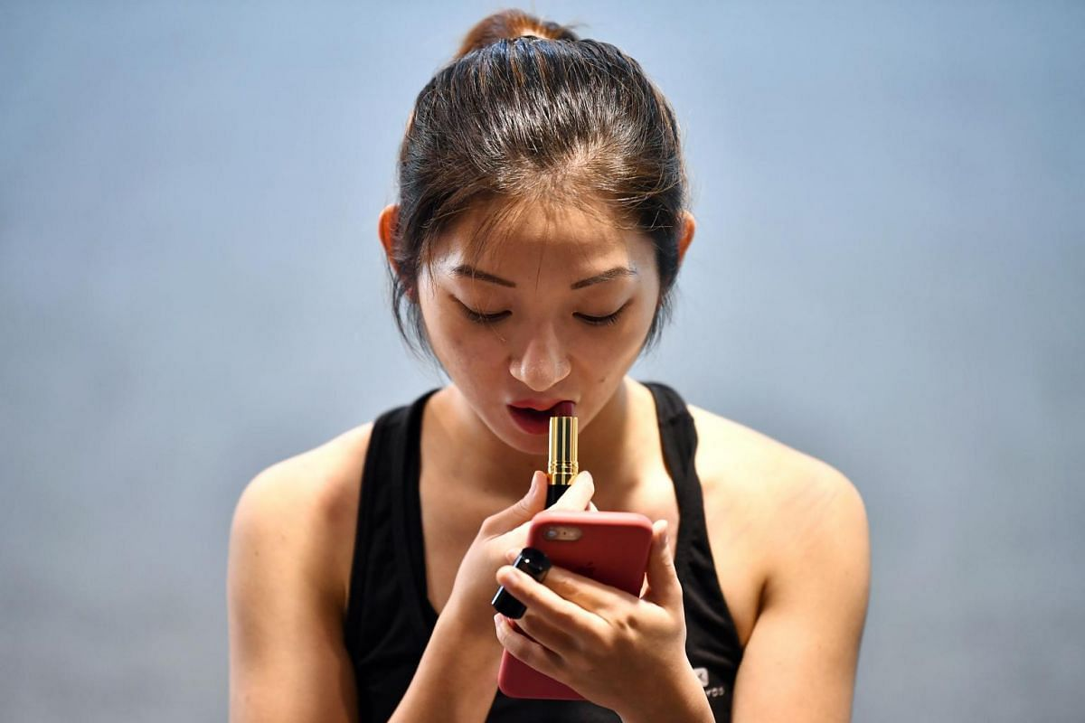Ms Miki Nomura, 24, co-founder and head coach of D'Gymnastique Academy, putting on lipstick during a training session at Shelton College International, on Feb 16, 2019.