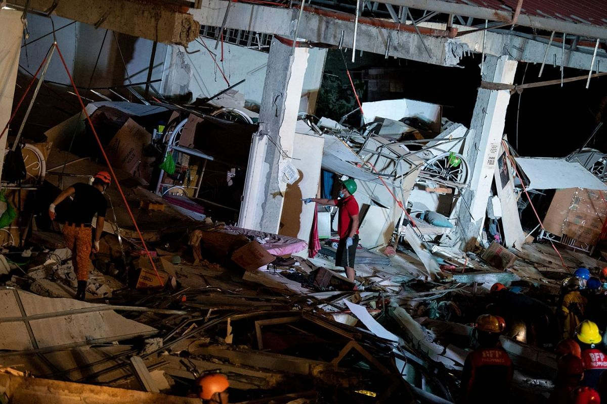 Rescue workers search for survivors in a collapsed Chuzon Super Market in Porac, Pampanga, after a powerful earthquake hit northern Philippines on April 22, 2019. PHOTO: AFP