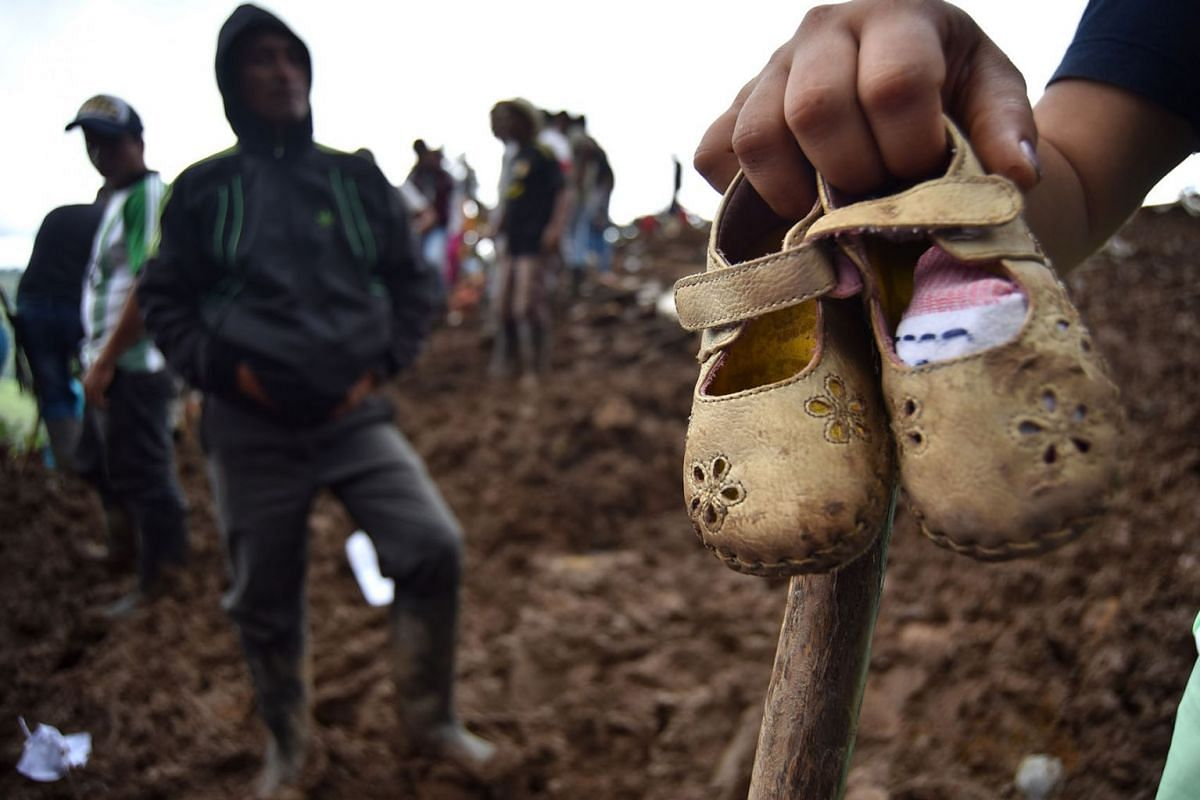 A person shows some children's shoes after a landslide, in the village of Portachuelo, in the municipality of Rosas, Cauca, Colombia, April 22, 2019. PHOTO: EPA-EFE