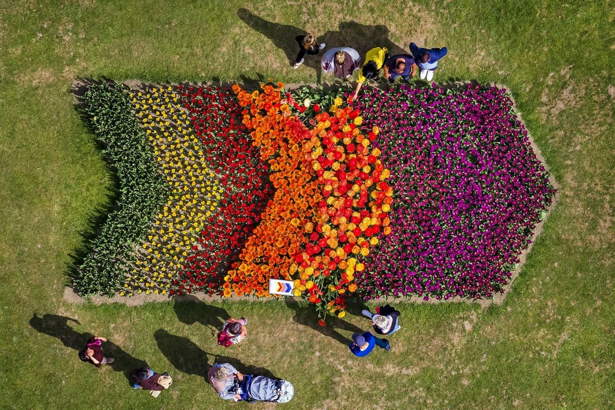 """A picture taken with a drone shows people enjoy the warm weather on Easter Monday and gather to see 120,000 tulips of more than 380 varieties in full bloom at the tulip festival in the """"Parc de l'Independance"""" in Morges, Switzerland, April 22, 2019."""