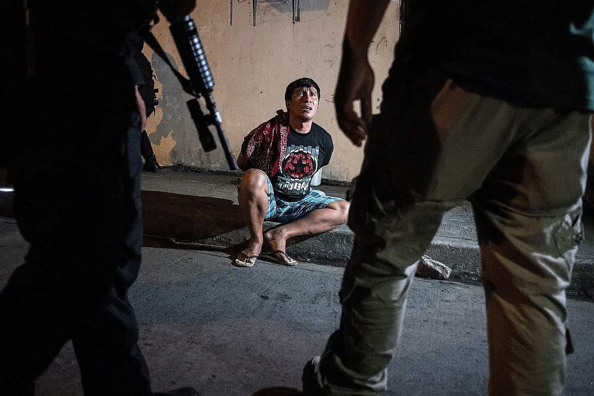 Male residents being rounded up for verification after police officers conducted a large-scale anti-drug raid in a slum community in Manila in July 2017. One resident was killed in the raid, according to police. Philippine Drug Enforcement Agency age