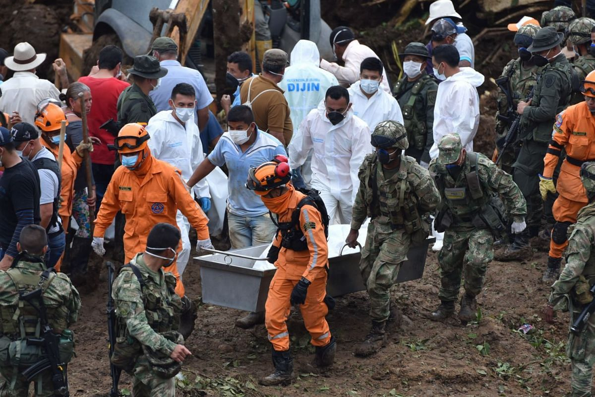 Volunteers, civil defence members and soldiers move two bodies recovered after a landslide in the village of Portachuelo, in the municipality of Rosas, Cauca, Colombia, on April 22, 2019.