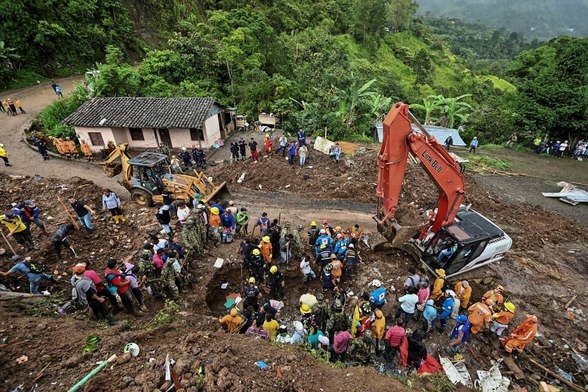 Civil defence members and firefighters search for victims after a landslide in Rosas.