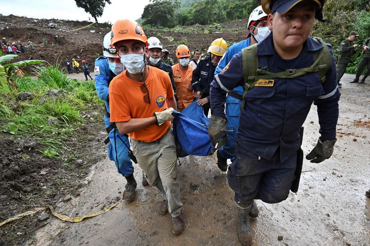 Civil defence members and firefighters carry a corpse after a landslide in Rosas.