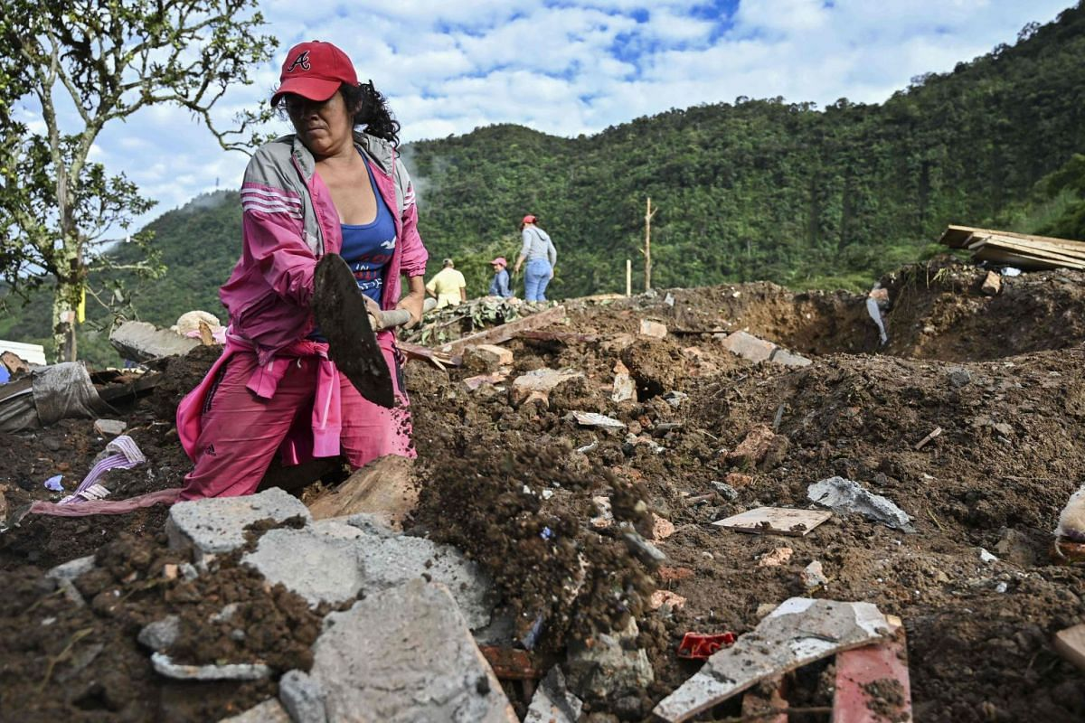 A woman searches for victims after a landslide in Rosas.