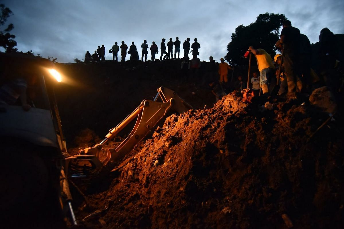 Firefighters and members of the army and civil defence look for survivors after a landslide in Portachuelo.