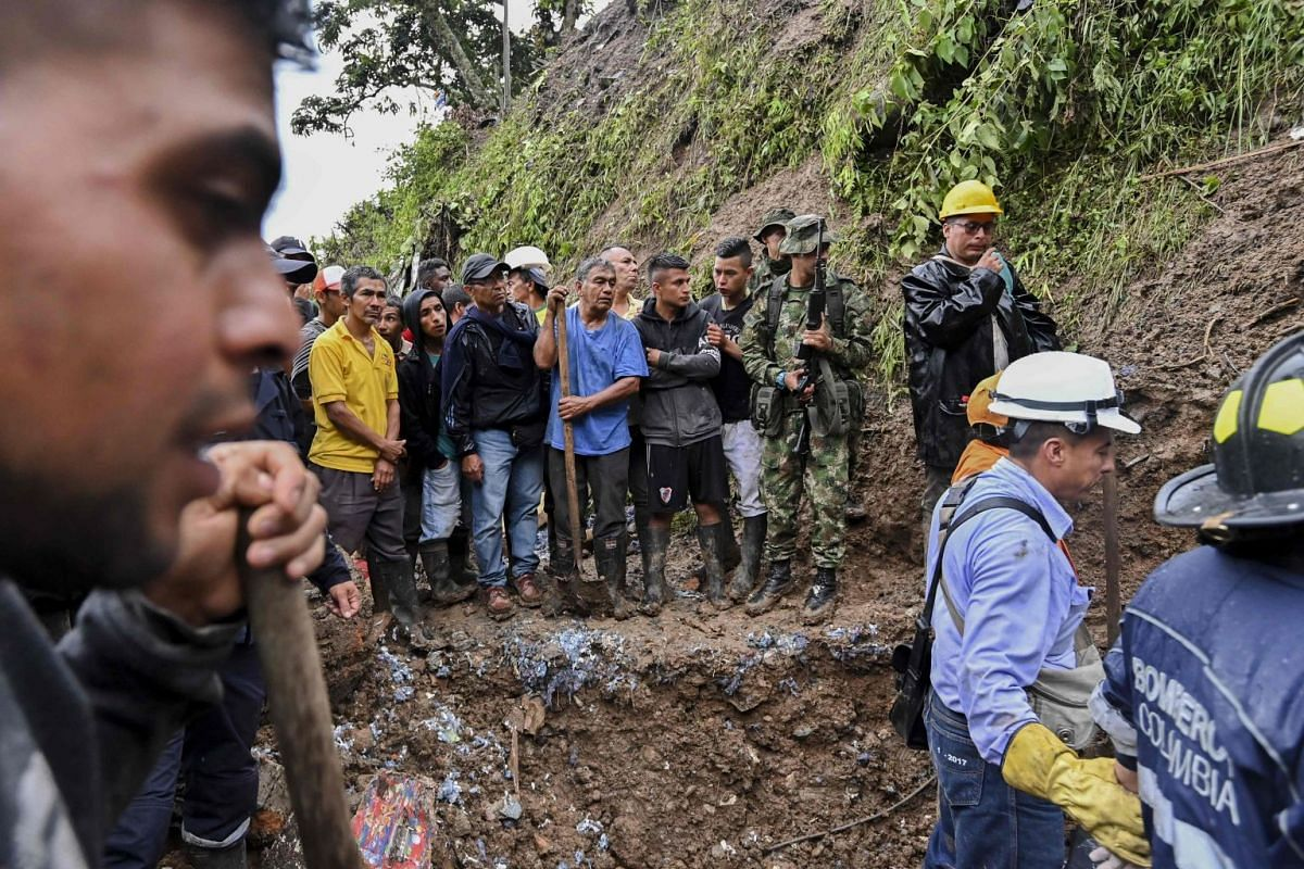 People watch as rescue workers recover a corpse after a landslide in Rosas.