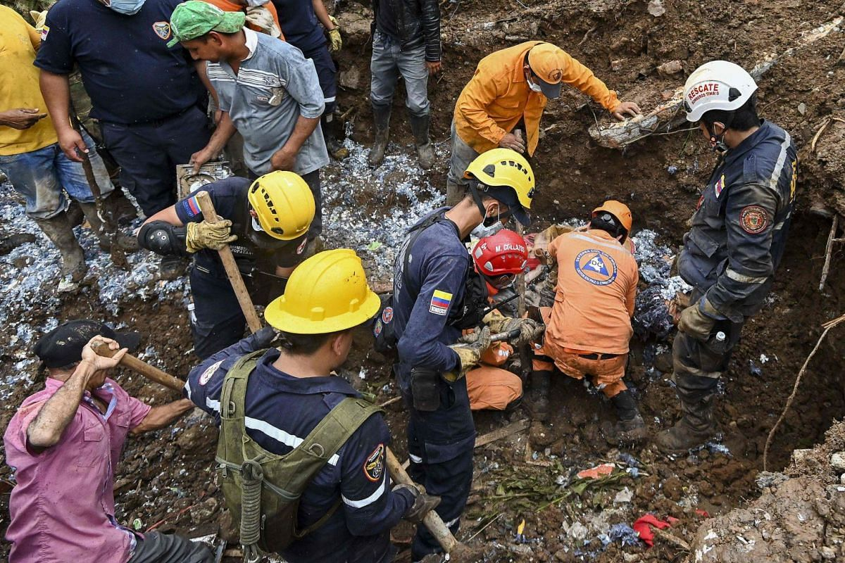 Rescue workers recover a corpse after a landslide in Rosas.