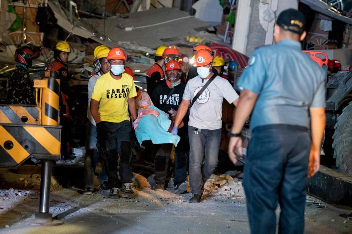 Rescue workers carry a victim from a collapsed Chuzon supermarket in Porac.