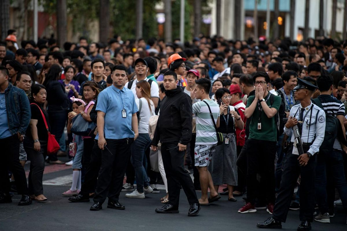 Office workers pile onto the streets as emergency alarms blare in Manila. Thousands of people flee high-rise buildings in the city.