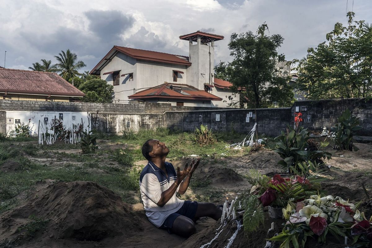 Melton Roy prays amid the graves during burials at Sellakanda Catholic Cemetery in Negombo, Sri Lanka, on April 23, 2019. The Islamic State claimed responsibility on Tuesday for the Easter Sunday bombings at churches and hotels in Sri Lanka that kill