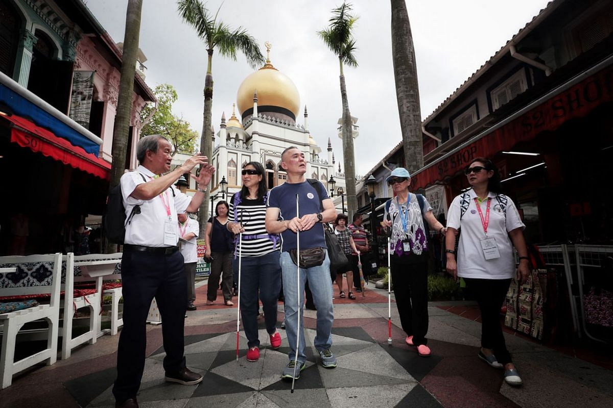 Senior ambassador Mr Chhua Bak Siang, 71, guiding visually impaired participants from Guide Dogs Singapore on a trip down memory lane in the Kampong Gelam heritage precinct on April 23, 2019, as part of the second leg of the Reminiscence Walks progra