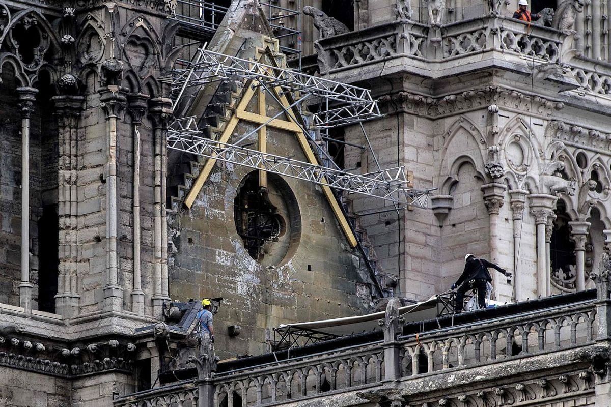 Workers install protective tarps on the roof of Notre-Dame de Paris cathedral in Paris on April 23, 2019, one week after a fire devastated the cathedral. PHOTO: AFP