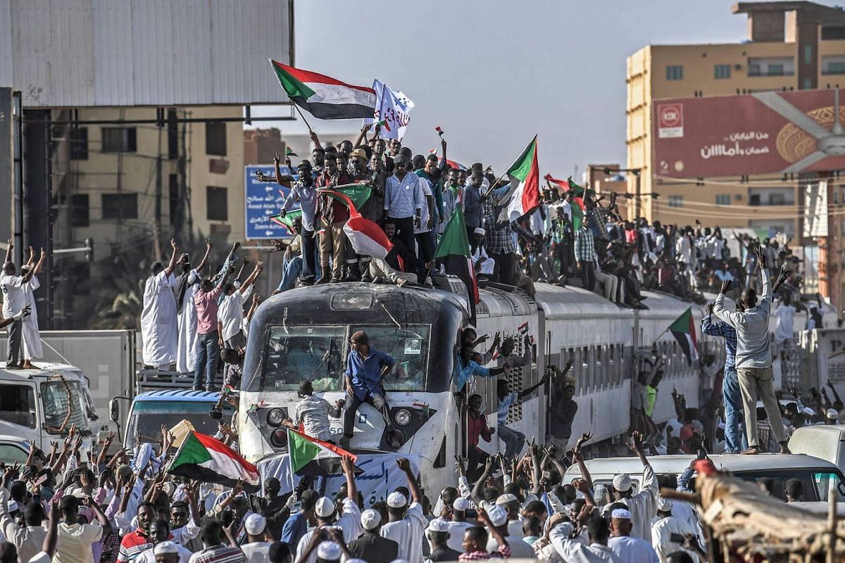 Sudanese protesters from the city of Atbara, sitting atop a train, cheer upon arriving at the Bahari station in Khartoum on April 22, 2019. PHOTO: AFP