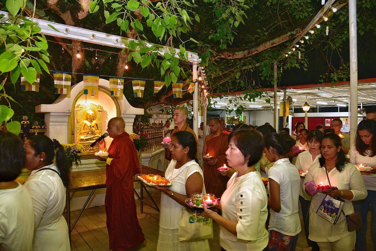 Venerable K. Gunaratana (with microphone) leading a procession around the bodhi tree compound at the Sri Lankaramaya Buddhist Temple on 24 April 2019, with attendees carrying plates of flowers and candles in memory of the victims of the bomb blasts i