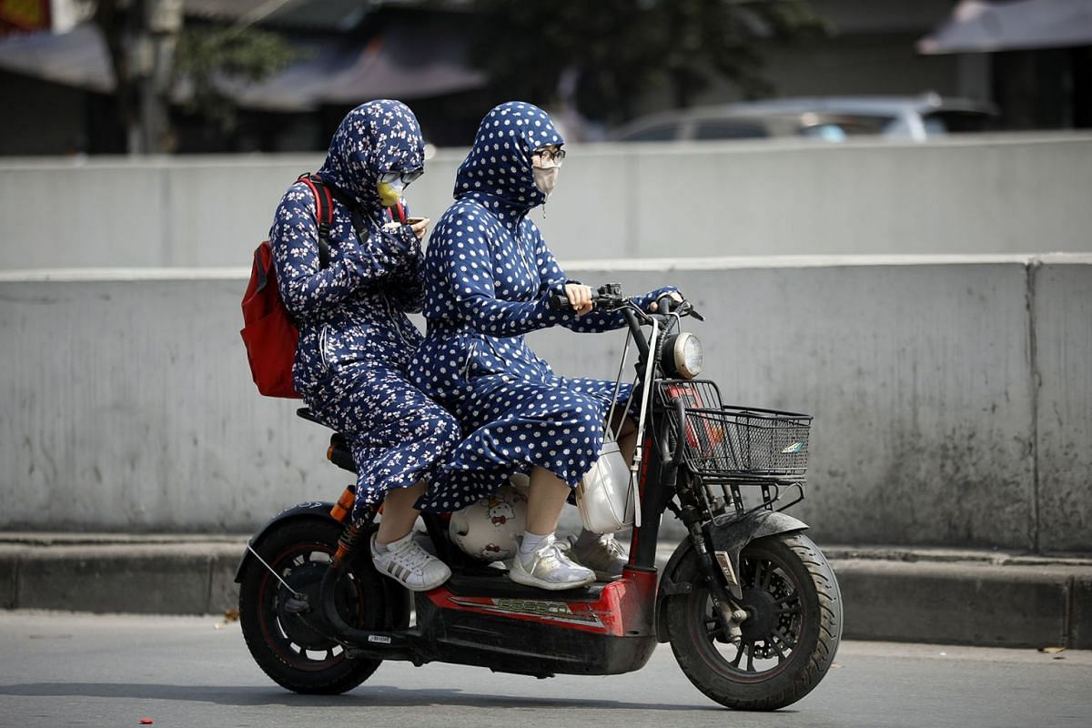 People wear clothing to protect them from the heat while riding along a street in Hanoi, Vietnam, April 24, 2019. PHOTO: EPA-EFE