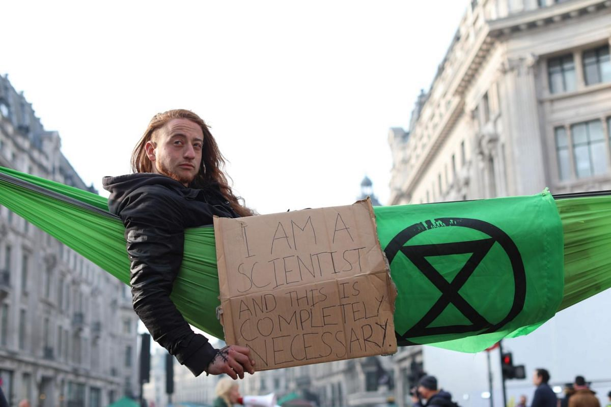 A climate change activist in a hammock occupying Oxford Circus in the busy shopping district of central London, on April 18, 2019, the fourth day of a protest by the Extinction Rebellion group.