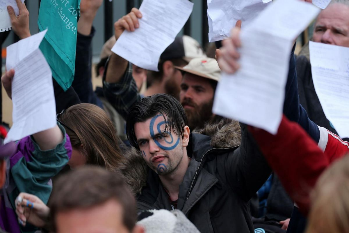 Climate change activists hold up letters addressed to their MPs as they attempt to approach the Houses of Parliament during the ongoing Extinction Rebellion climate change demonstration, in central London, on April 23, 2019.