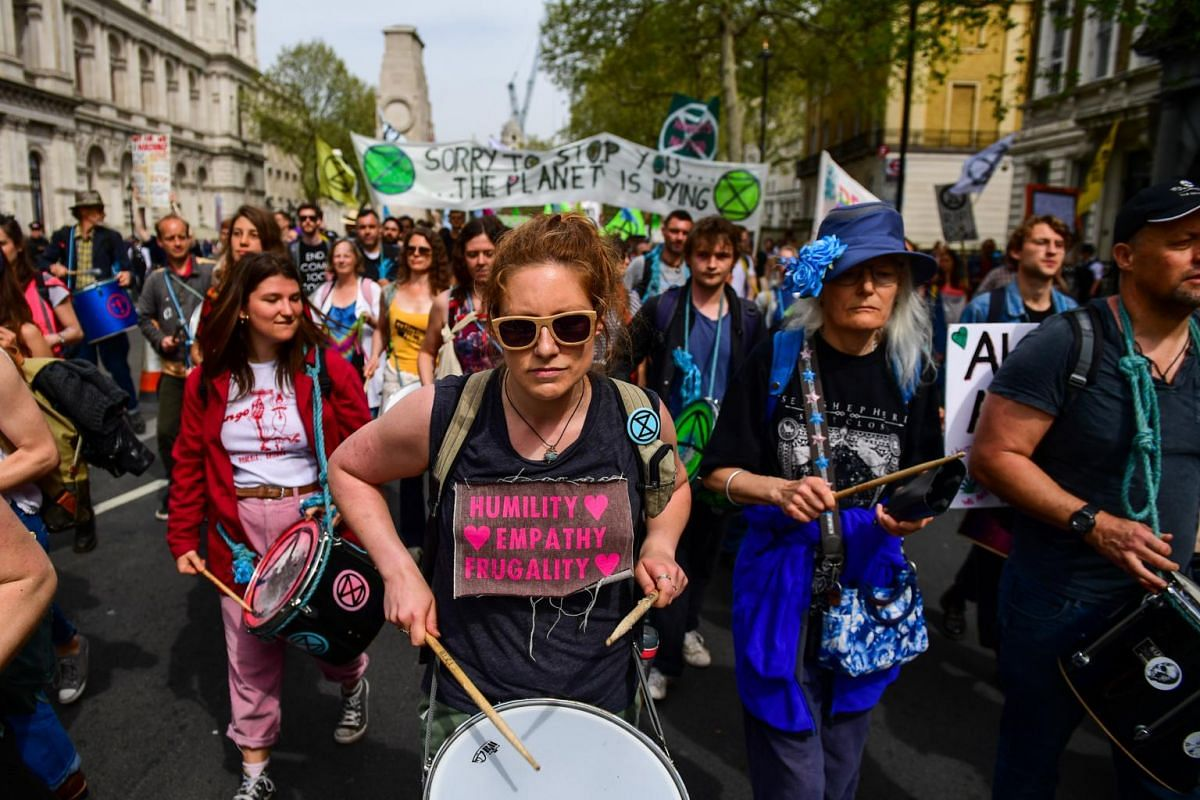 Climate activists from the Extinction Rebellion group march along Whitehall towards the Houses of Parliament in London, on April 23, 2019.