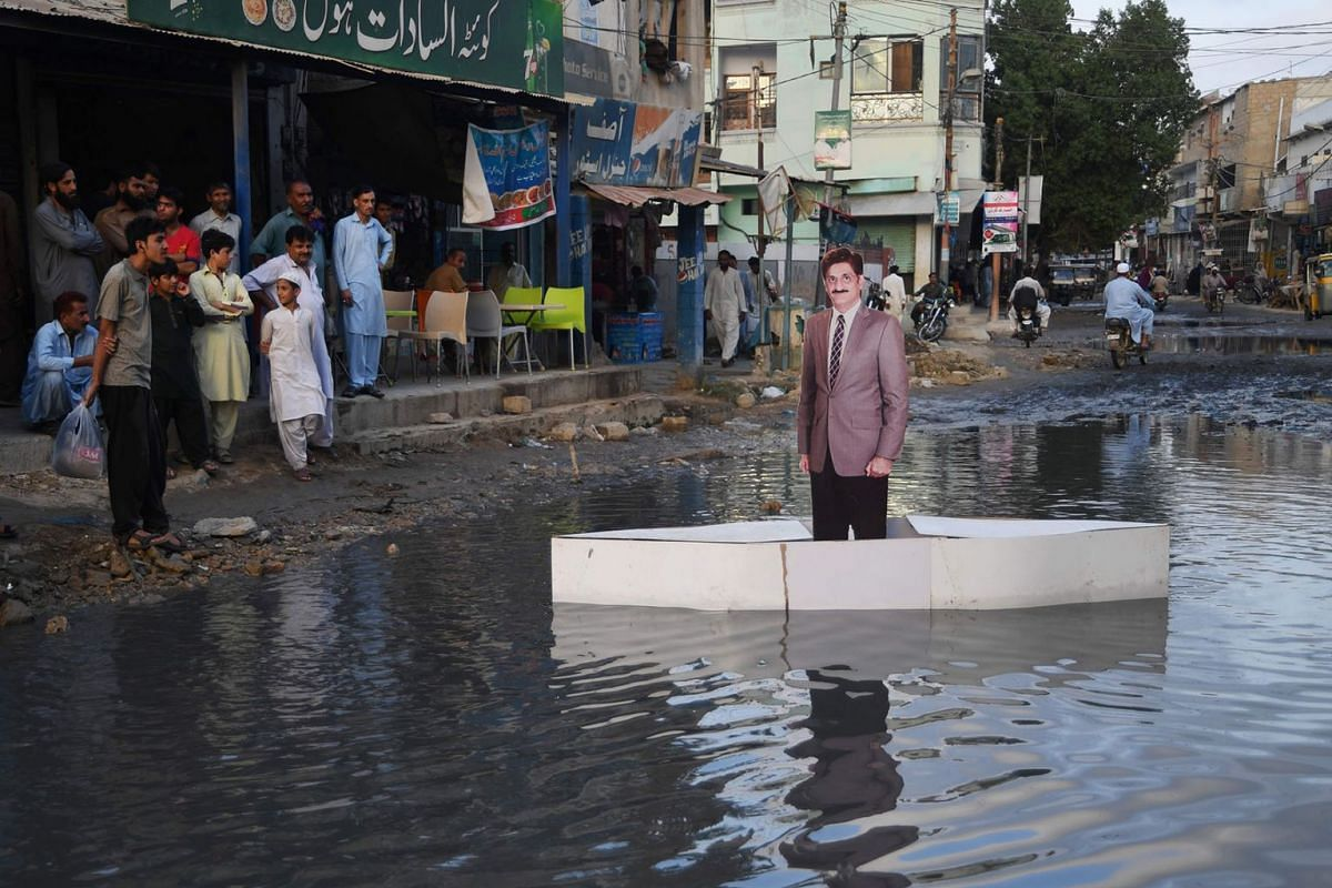Local residents look at a boat with a cutout of Sindh Province Chief minister Murad Ali Shah on drainage water placed by activists of the civil society organisation Fixit at a residential area in Karachi to highlight the issue of sewerage water in th