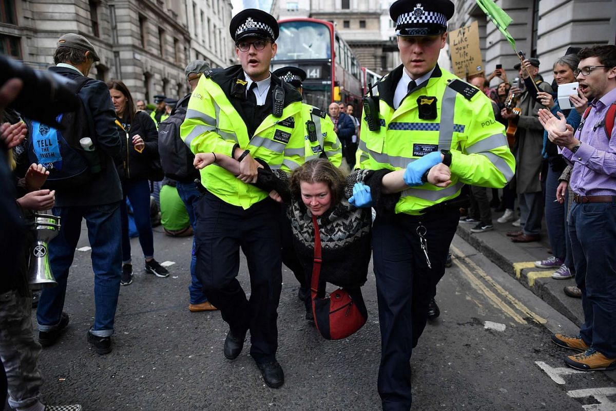 Police officers remove climate change activists from their road blockades around the Bank of England in the City of London financial district in London on April 25, 2019, during environmental protests by the Extinction Rebellion group. PHOTO: AFP