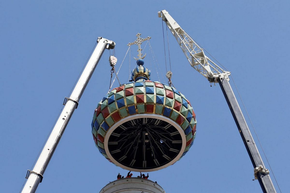 Workers use cranes to lift up a dome before installing it on the top of Kazan Cathedral's bell tower in Stavropol, Russia April 25, 2019. PHOTO: REUTERS