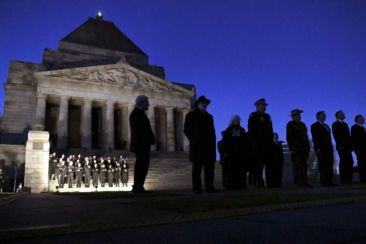 People gathering on the steps of the Shrine of Remembrance at an Anzac Day dawn service in Melbourne.