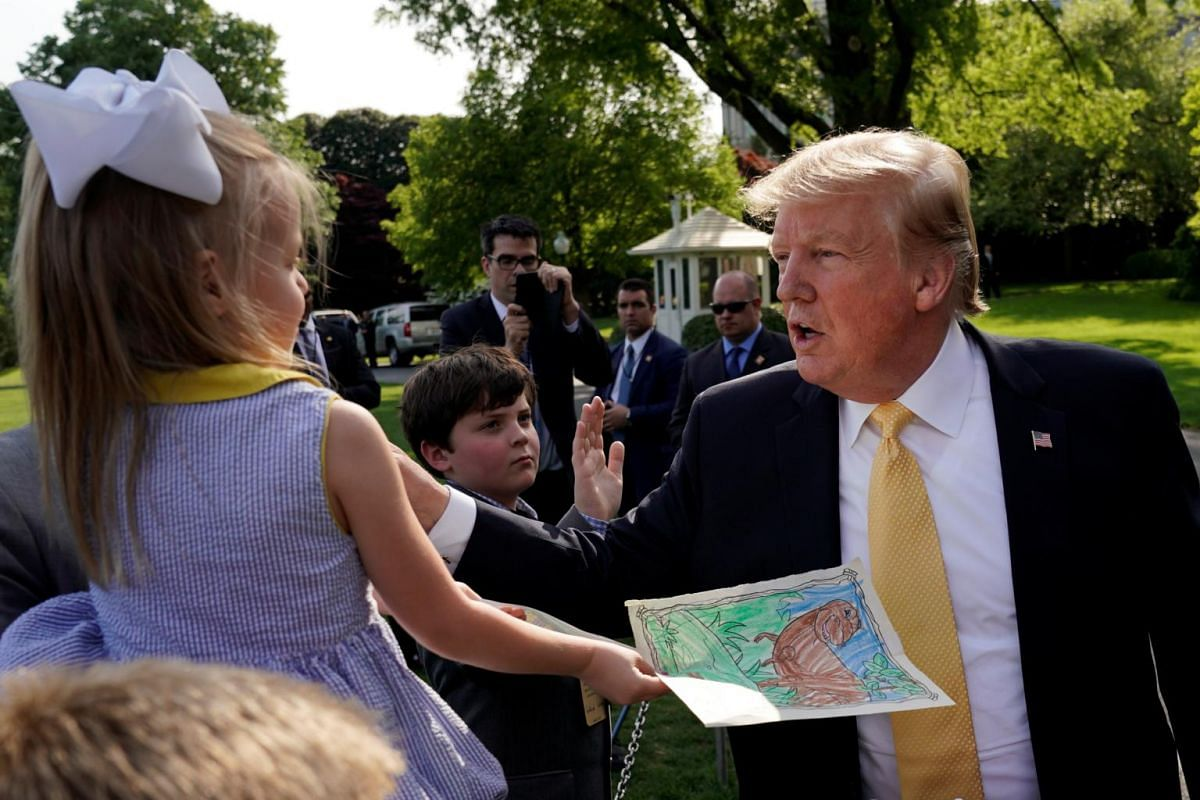 A young girl hands a drawing to US President Donald Trump during Take Our Daughters and Sons to Work Day.