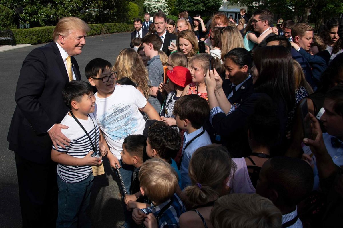 US President Donald Trump poses for a photo as he greets children of journalists and White House staff.