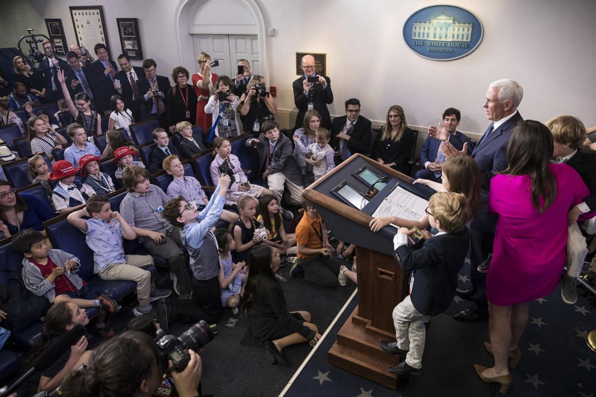 Vice-President Mike Pence and Press Secretary Sarah Huckabee Sanders answer questions from children of journalists and White House staff. Ms Sanders' children stand at the podium with her.