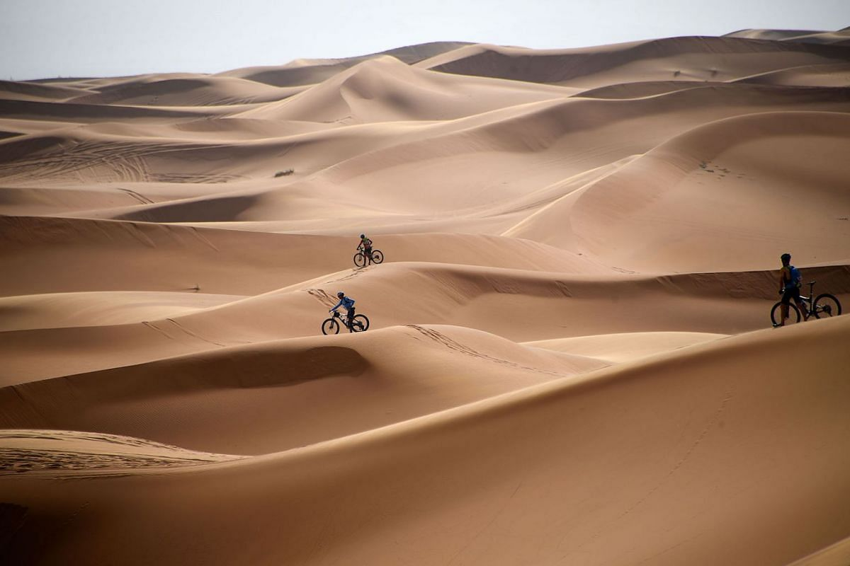 Competitors ride their bikes along sand dunes during the Stage 1 of the 14th edition of Titan Desert 2019 mountain biking race around Merzouga in Morocco on April 28, 2019.