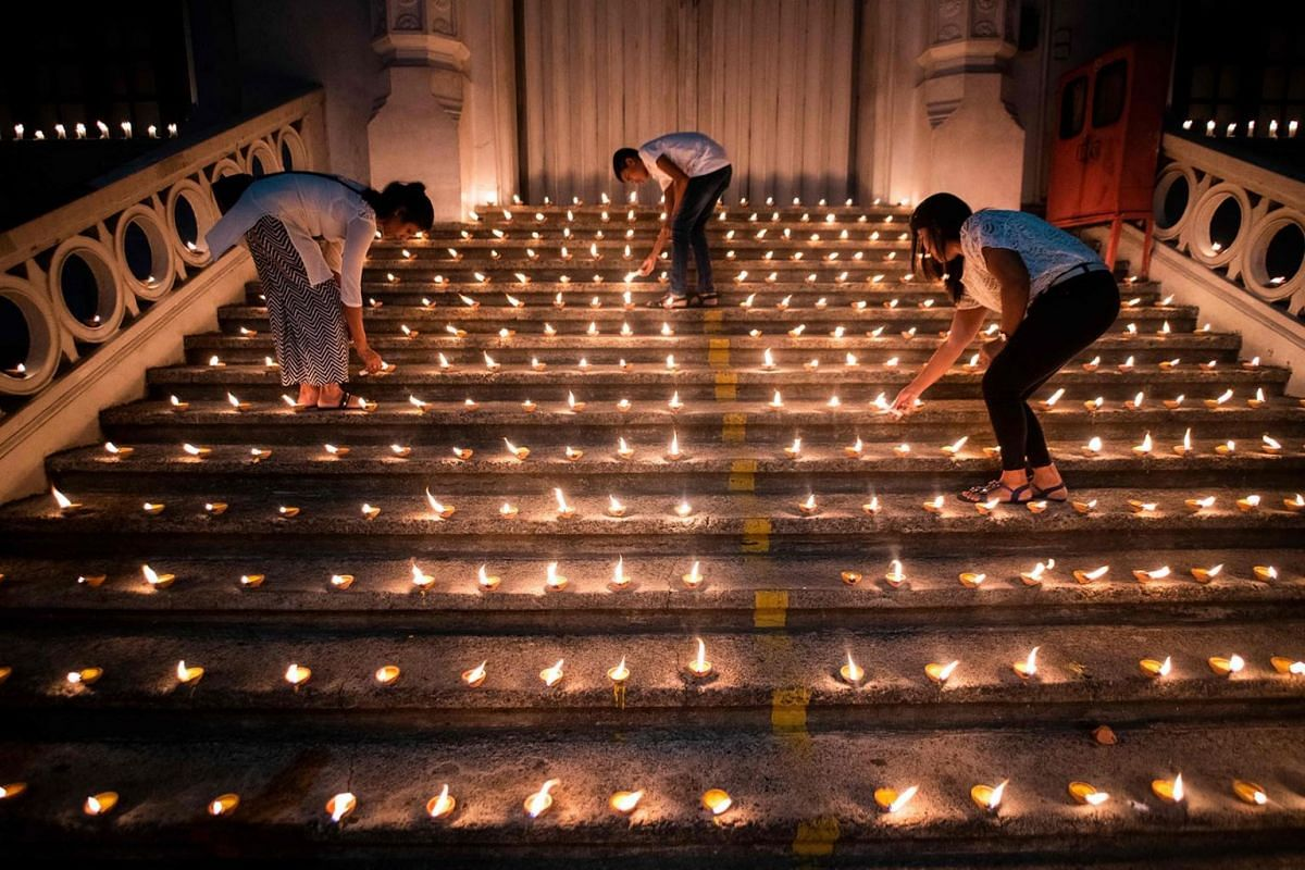 Mourners light candles during a vigil in memory of the bomb blast victims in Colombo on April 28, 2019, a week after a series of bomb blasts targeting churches and luxury hotels on Easter Sunday in Sri Lanka. Sri Lanka's churches remained shut on Apr